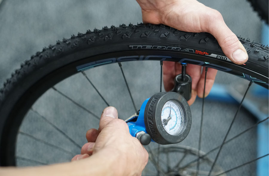 Inflating tyre with pressure gauge visible