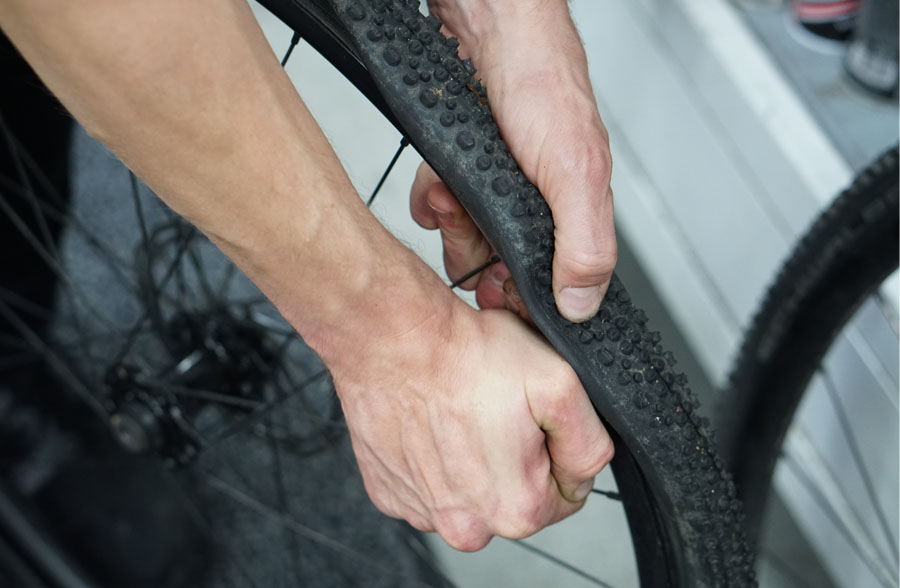 Hands removing old tyre from wheel